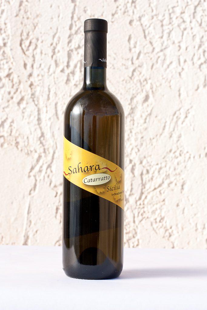 Bottiglia di Catarratto ~Sahara~ (vino bianco) con etichetta obliqua gialla.